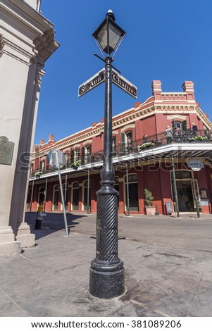 New Orleans, LA/USA - circa February 2016: Pole with street signs and old Colonial House with ironwork galleries on the Streets of French Quarter decorated for Mardi Gras in New Orleans, Louisiana - stock photo