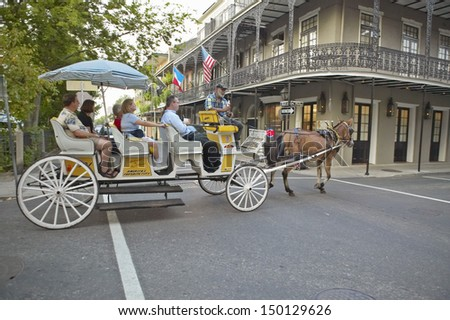 NEW ORLEANS, LOUISIANA - CIRCA 2004: Horse Carriage and tourists in French Quarter of New Orleans, Louisiana - stock photo
