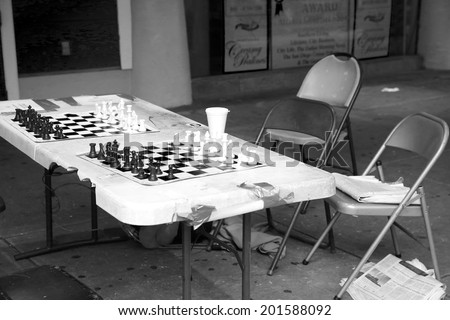 NEW ORLEANS, LOUISIANA, JUNE 24, 2014: An open chess game along the sidewalk on Bourbon Street in New Orleans invites others to join the game. New Orleans, Louisiana, June 24th, 2014 - stock photo
