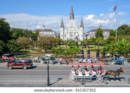 New Orleans, Louisiana, USA - October 28, 2014: The street in front of Jackson Square in French Quarter is a big attraction, often filled with traffics of horse-drawn tourist carriages and modern cars - stock photo