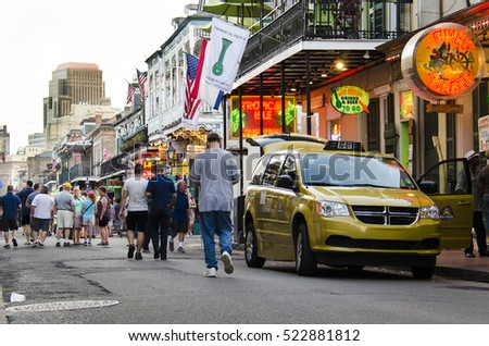 New Orleans, USA - July 8, 2015: A crowd of people walk in the evening on famous Bourbon Street in Louisiana.