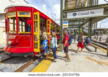 NEW ORLEANS, USA - JULY 16, 2013: people enter the  Streetcar Line in New Orleans, USA. Revamped after Hurricane Katrina in 2005, the New Orleans Streetcar line began electric operation in 1893. - stock photo