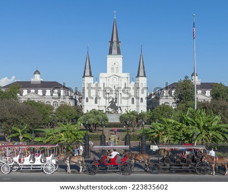 NEW ORLEANS, USA - OCTOBER 11, 2014: Horse-drawn carriages wiat on street in front of Saint Louis Cathedral in New Orleans on a sunny Saturday morning ready for the influx of tourists soon to arrive. - stock photo