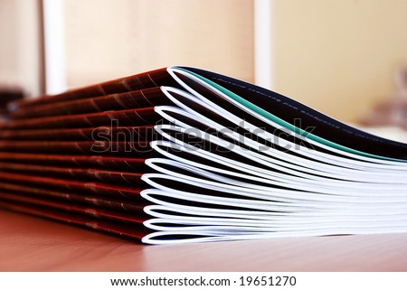 new pink magazines  in pile over desk - stock photo