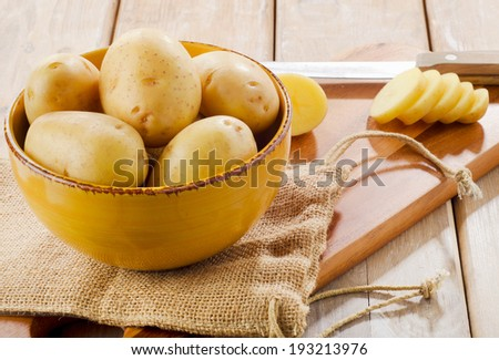 New potatoes in a bowl on wooden table - stock photo