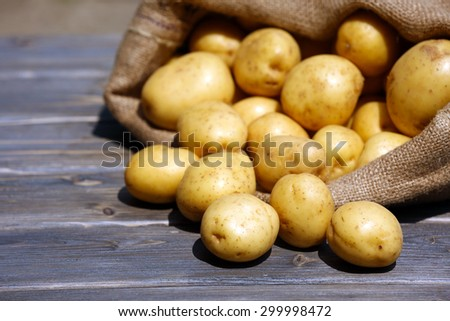New potatoes in sackcloth bag on wooden table, closeup - stock photo