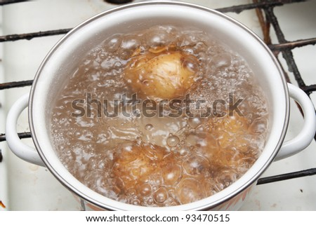 New potatoes simmering in boiling water - stock photo