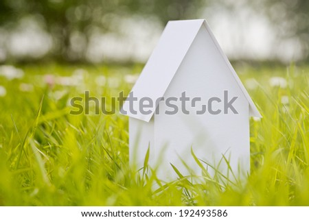 New property - a white paper model house standing on a green grass field. - stock photo