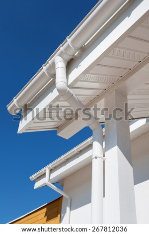 New rain gutter on a white home against blue sky - stock photo