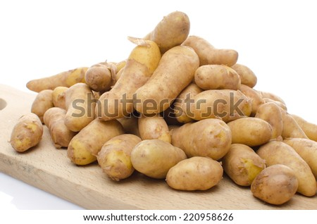 New rattes potatoes on a wooden board, isolated on white - stock photo
