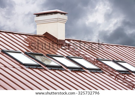 new red metal roof with skylights and chimney - stock photo