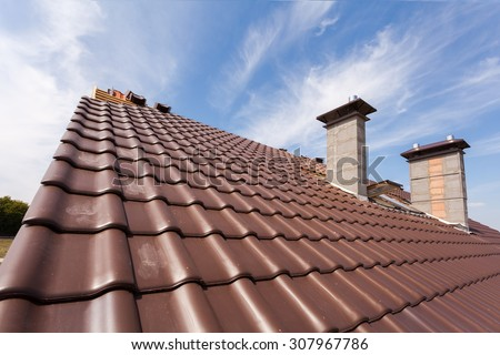 New red tiled Roof with chimneys - stock photo