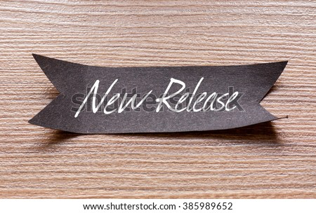 New Release words written on Black papper with wooden background - stock photo