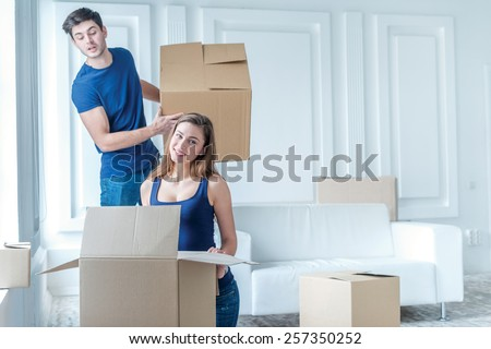 New repair and relocation. Loving couple enjoys a new apartment and keep the box in his hands while young and beautiful couple in love standing near the couch in an empty apartment among boxes - stock photo
