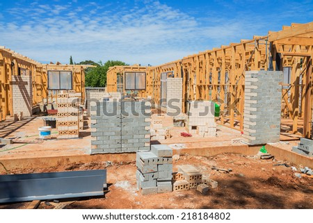 New residential construction home framing against a blue sky. - stock photo