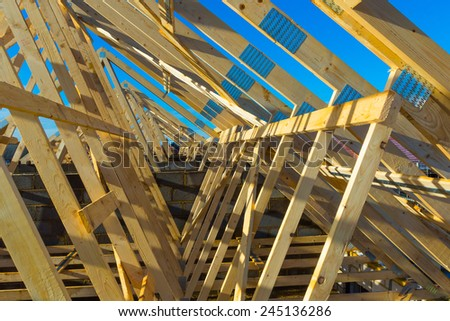 New residential construction home framing against a blue sky  - stock photo
