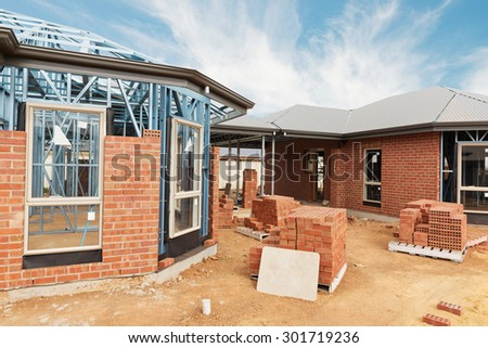 New residential construction home from brick with metal framing against a blue sky - stock photo