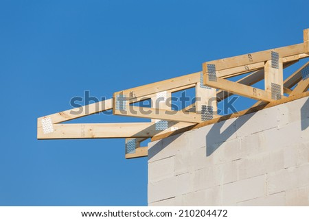 New residential construction roof home framing against a blue sky - stock photo