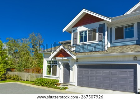 New residential townhouse on sunny day with wide garage door and concrete pathway in front. British Columbia, Canada. - stock photo