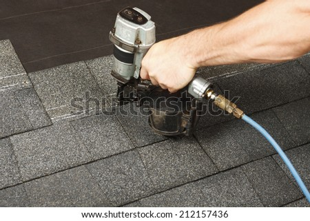 New roof shingle being applied - stock photo
