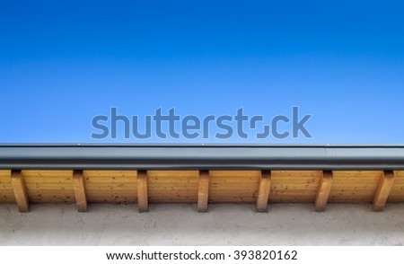 New roof top detail with copper water gutter, against blue skies. - stock photo