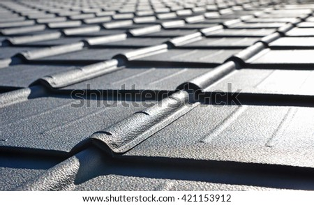 new roof with black sheet metal and background of blue sky - stock photo