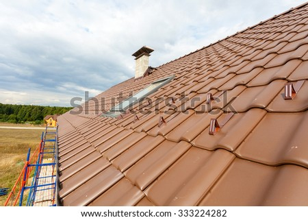 New roof with natural red tile and chimney. House under construction - stock photo