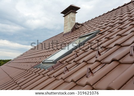 New roof with skylight, natural red tile and chimney - stock photo