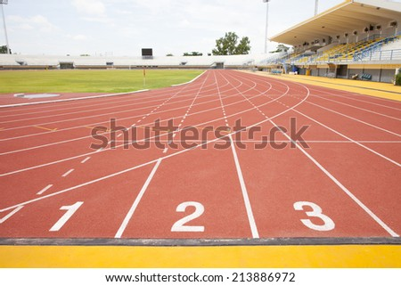 New running track and grandstand Red treadmill at the stadium with the numbering - stock photo