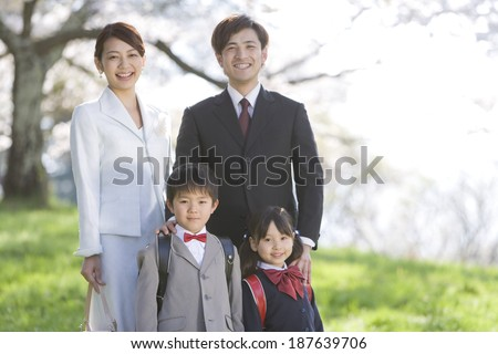 new school children and parents standing still on lawn - stock photo