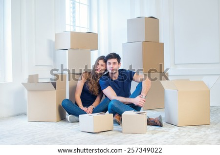 New shifting and relocation. Loving couple enjoys a new apartment and keep the box in his hands while young and beautiful couple in love sitting on the floor in an empty apartment among boxes - stock photo