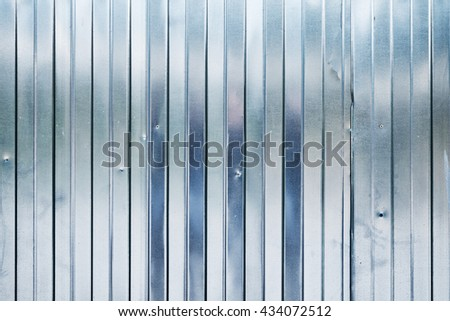 New shining corrugated metal fence, industrial wall background photo texture