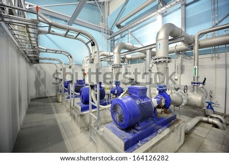new shiny pipes and large pumps in industrial boiler room - stock photo