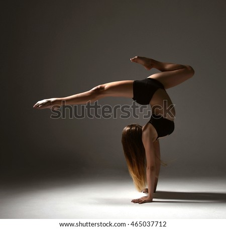 New slim jazz modern contemporary style woman ballet dancer dancing pose dark studio background
