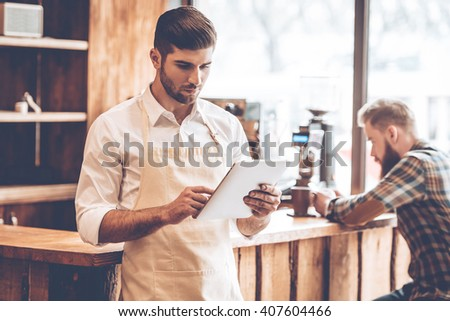 New solutions for his business. Young handsome man in apron using his digital tablet while standing at cafe with customer at background - stock photo