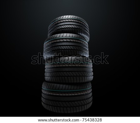 new summer tires stacked, over black, studio shot - stock photo