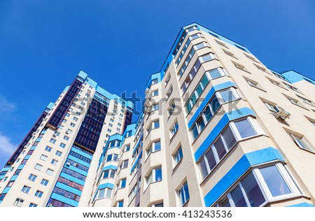 New tall modern apartment buildings against blue sky background - stock photo
