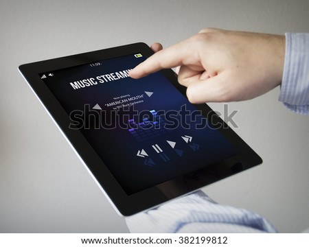 new technologies concept: hands with touchscreen tablet streaming music online. Screen graphics are made up.