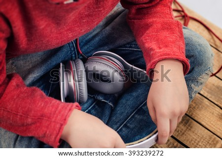 New technology, home, leisure, and music concept. Boy sitting with crossed legs and holding headphones - stock photo