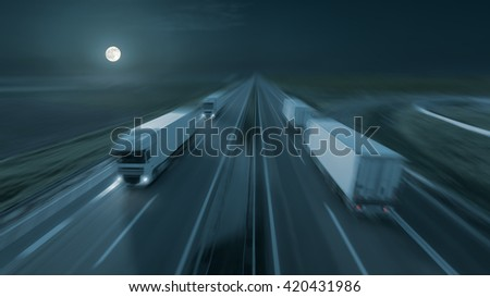 New temperature controlled trucks driving fast towards the moon at night. Speed blurred motion drive on the freeway. Freight scene on the motorway as speed concept. - stock photo