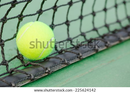 New tennis ball and black net on green hard court - stock photo