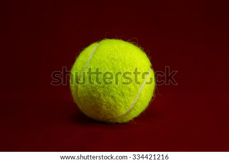 New tennis ball isolated on red background