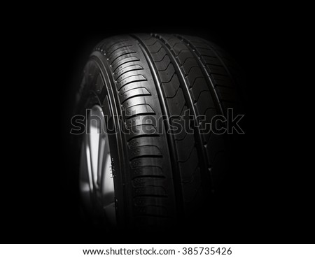 new  tire with modern tread on black background brightly lit from above.  - stock photo