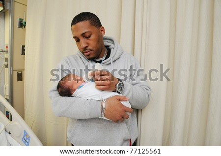 New Tired Family Father Holding Feeding Newborn Infant Baby in Hospital Room Just after Birth - stock photo
