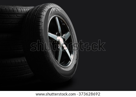 new tires are close to each other on an isolated dark background - stock photo
