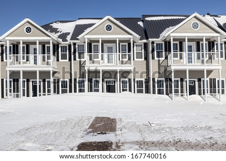 New townhouses under a layer of freshly fallen snow. - stock photo