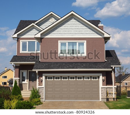 New two-storied white-brown brick cottage with beige garage and white roof. - stock photo