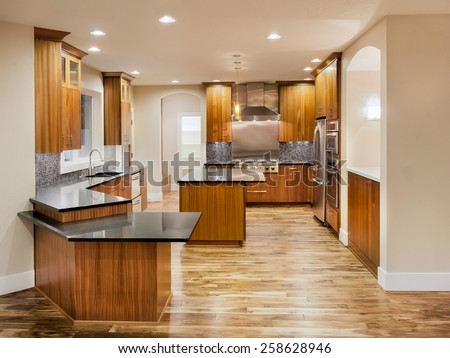 New Unfurnished Kitchen in Luxury Home with Island, Sink, Cabinets, and Hardwood Floors - stock photo