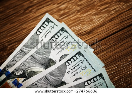 new 100 US dollars 2013 edition banknotes (bills) on wooden background