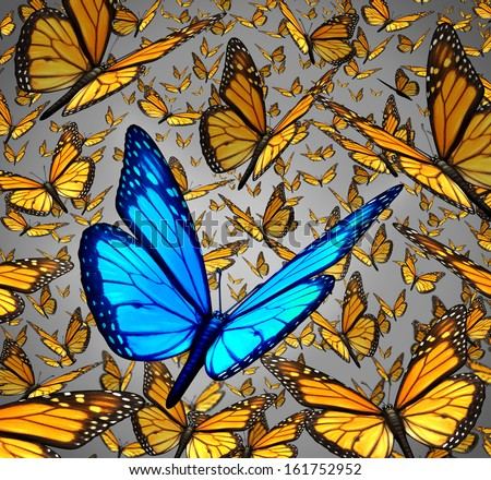 New vision standing out from the crowd business concept as a symbol of individuality and innovative thinking as a group of Monarch butterflies flying with a single special insect colored blue. - stock photo